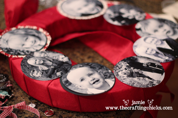 Red ribbon wrapped wreath with black and white family photos laid around it.