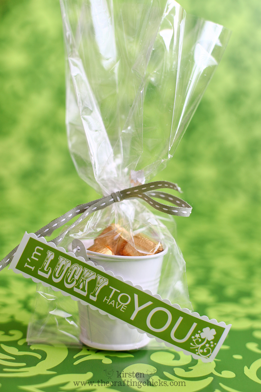 """Green background withe small white buckets filled with gold wrapped candies in a clear cellophane bag and a green ribbon. A printable tag is attached that says """"I'm lucky to have you."""""""