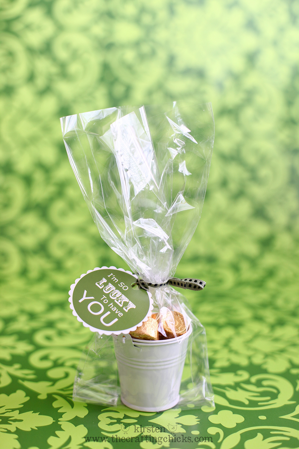 """Green background withe small white buckets filled with gold wrapped candies in a clear cellophane bag and a green ribbon. A printable tag is attached that says """"I'm so lucky to have you."""""""