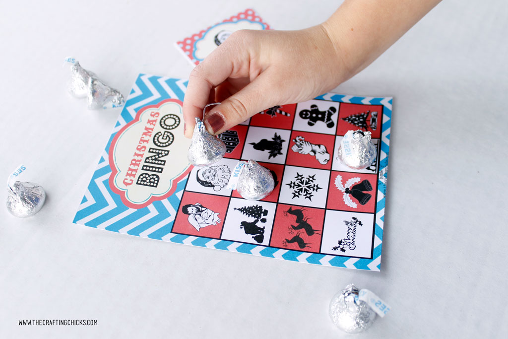 Free Printable Christmas Bingo Game with child's hand playing the game with Hershey Kisses.