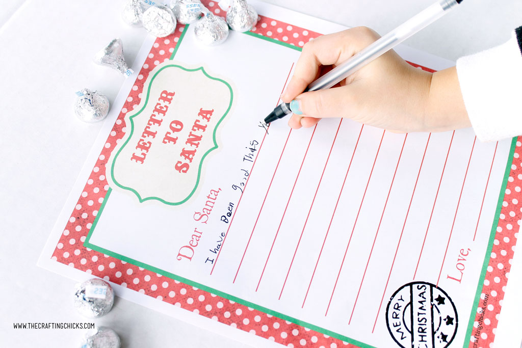 Child writing on Free Printable Letters to Santa with pens and Hershey Kisses.