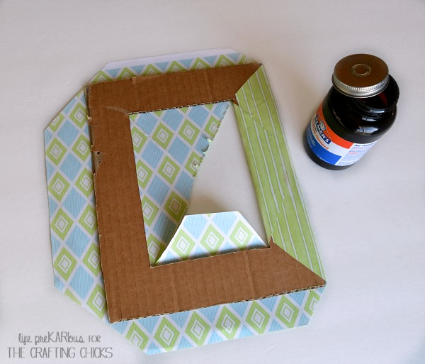 Use scrapbook paper and cardboard to make a cute photo mat