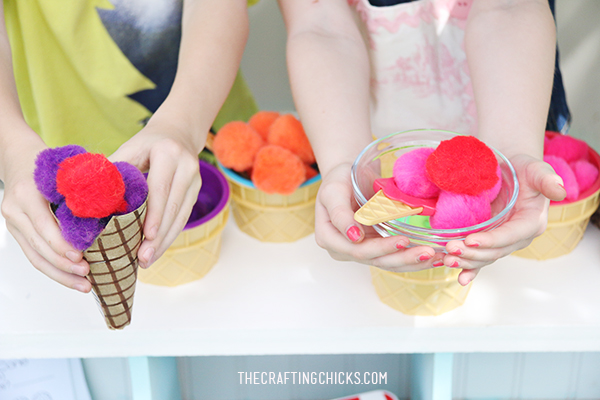 Children's hand holding a cardboard ice cream cone filled with pompoms and a glass bowel filled with pompoms for ice cream