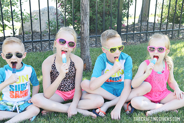4 kids sitting in the shade eating popsicles
