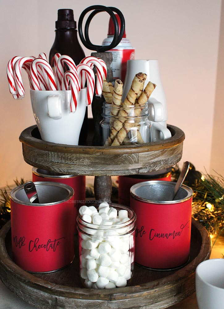 Rustic 2-tiered stand with hot chocolate mix, candy canes, marshmallow, mugs and whipped cream to make a Hot Chocolate Station.