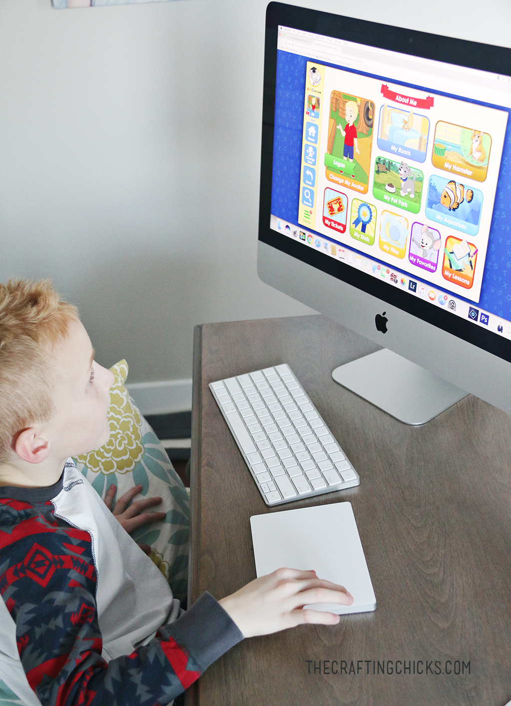little boy sitting at desk playing ABC Mouse to learn