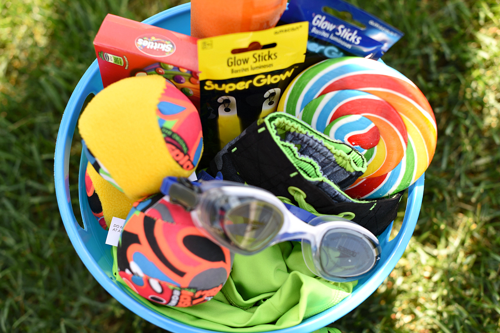 Blue sand bucket full of water toys, goggles, glow sticks and candy to make a summer gift.