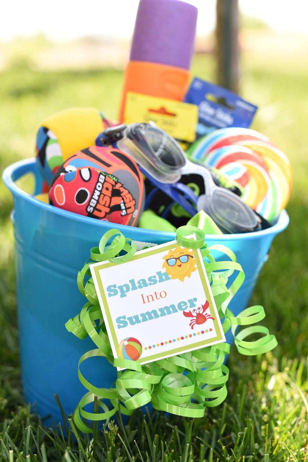 Sand bucket with water toys, goggles, and candy to make a gift.