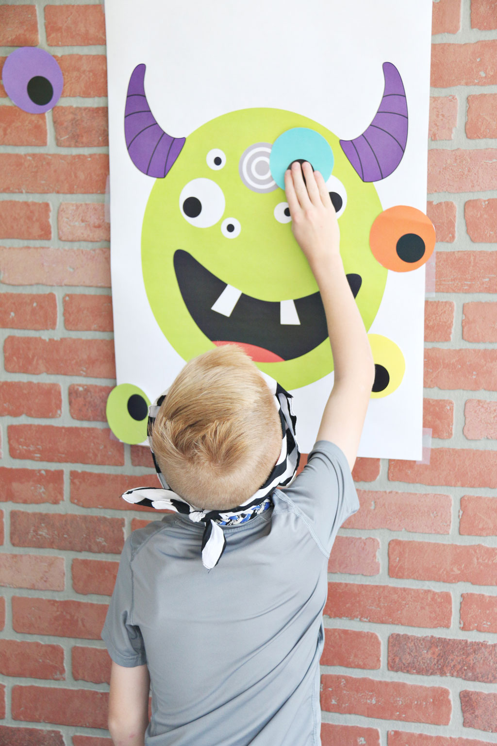 Little boy playing Pin the Eye on the Monster Halloween Game
