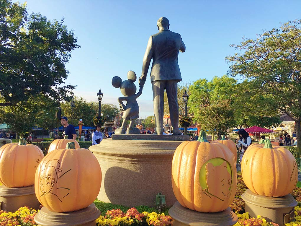 Statue of Walt Disney and Mickey Mouse in Disneyland with Pumpkins surrounding.