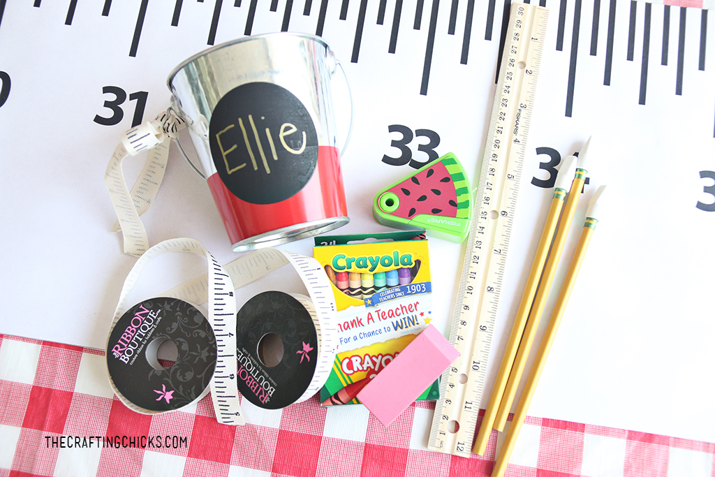 small tins with children's names on them with crayons, rulers, and pencils for a back to school gift idea