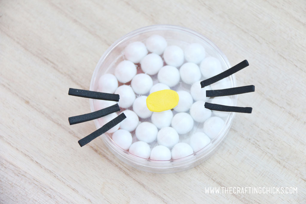 Adding a yellow nose and Black foam whiskers added to a clear round favor container filled with white Sixlets to make a Hello Kitty Face