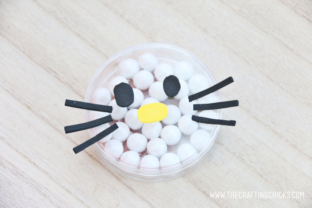 Add black foam eyes to the yellow foam nose Black foam whiskers added to a clear round favor container filled with white Sixlets to make a Hello Kitty Face