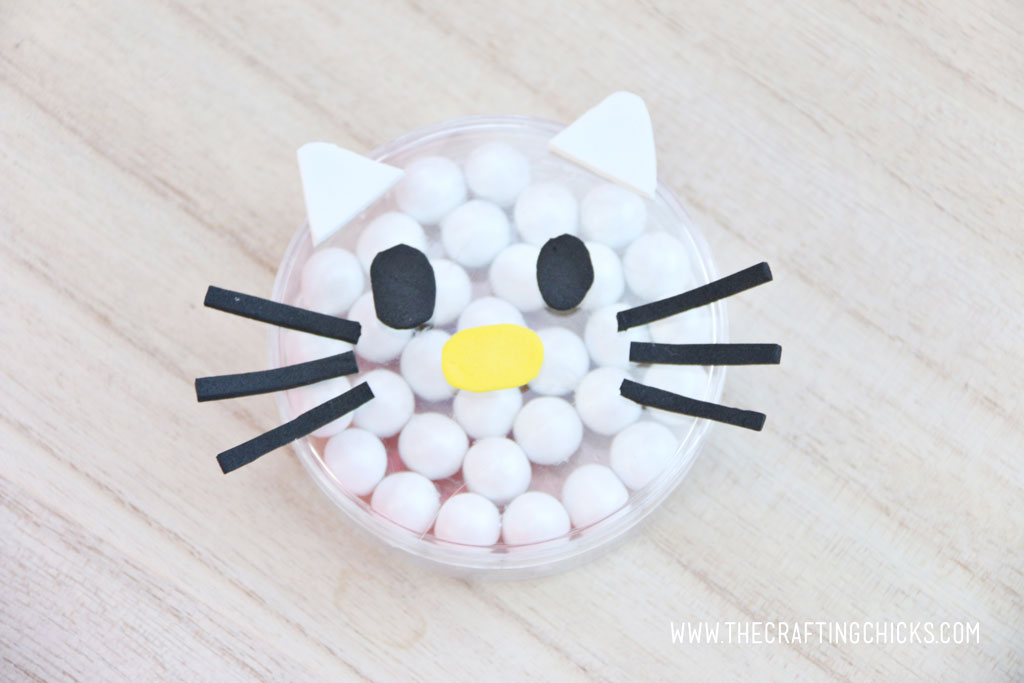 White foam ears added to a clear round favor container filled with white Sixlets to make a Hello Kitty Face