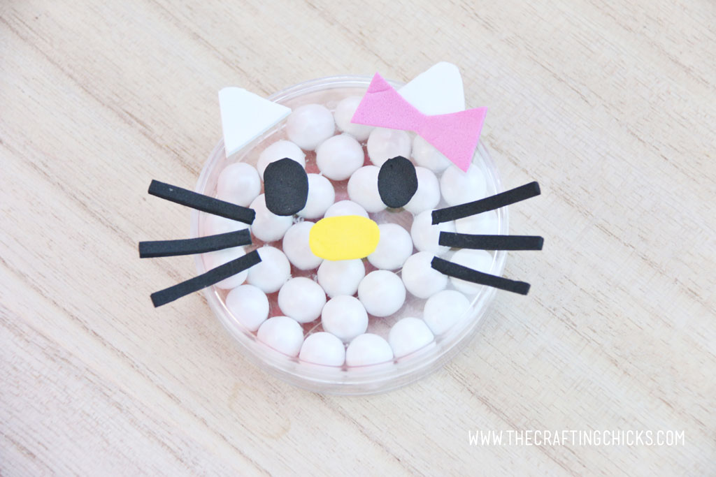 Pink foam bow added to a clear round favor container filled with white Sixlets to make a Hello Kitty Face