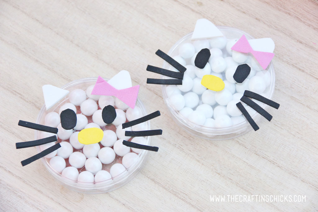 Small clear candy dishes filled with white round candies and decorated to look like Hello Kitty with foam stickers