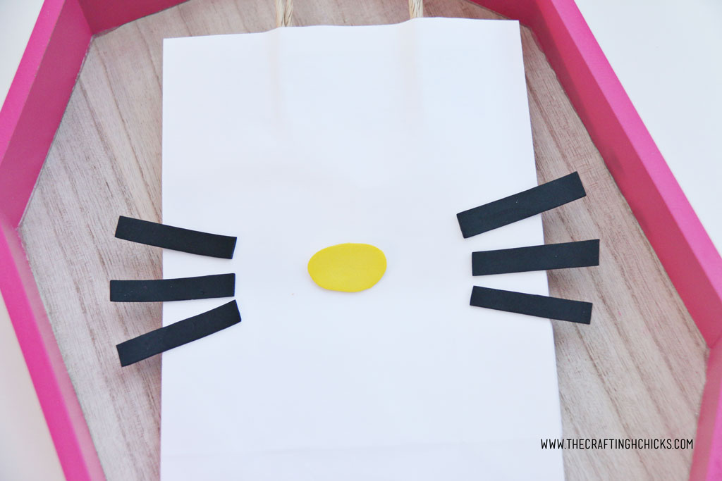 Yellow nose and black whiskers on a white gift bag to make a DIY Hello Kitty Bag