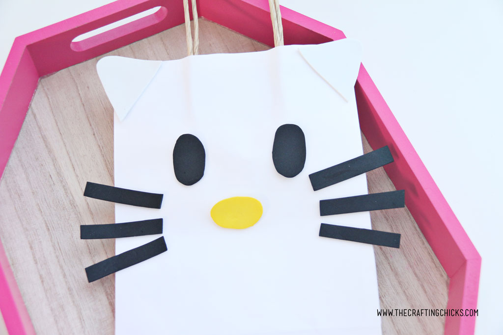White cat ears and black eyes added to white gift bag to make a DIY Hello Kitty Gift Bag