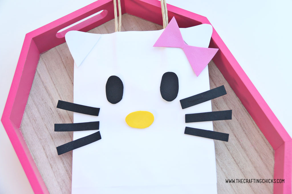 Pink bow added to white gift bag to make a DIY Hello Kitty Gift Bag