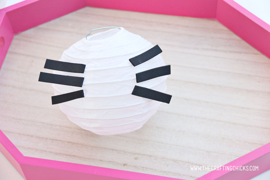 White mini paper lantern with black stripes of craft foam to make Hello Kitty DIY Paper Lanterns