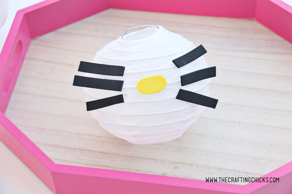 Yellow foam nose added to white mini paper lantern with cut out foam shapes to make Hello Kitty DIY Paper Lanterns