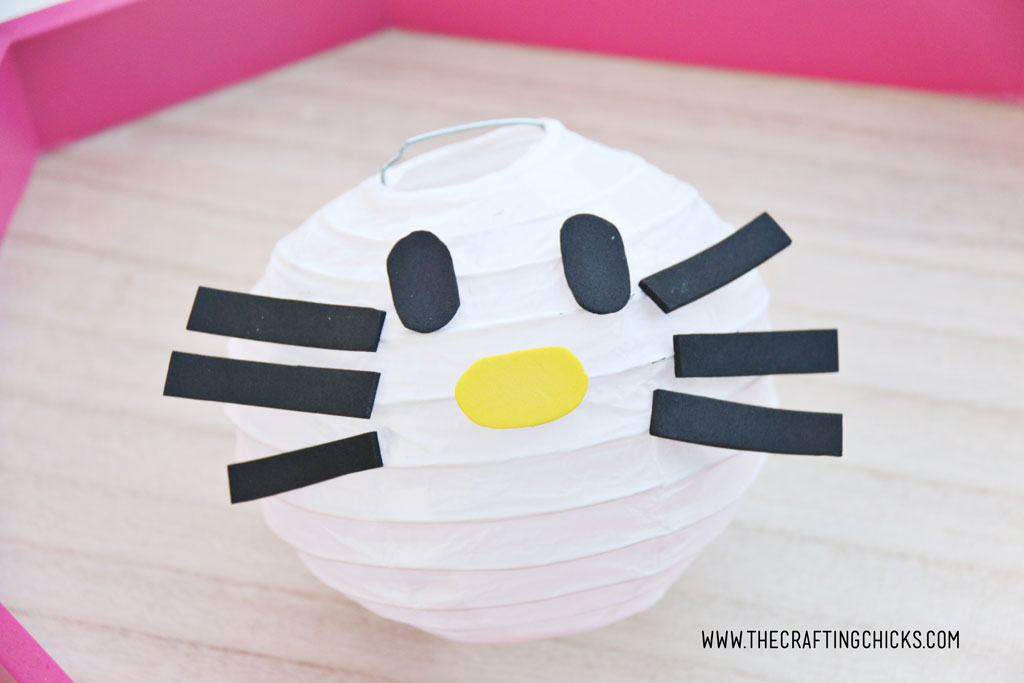 Black foam oval eyes White mini paper lantern with cut out foam shapes to make Hello Kitty DIY Paper Lanterns