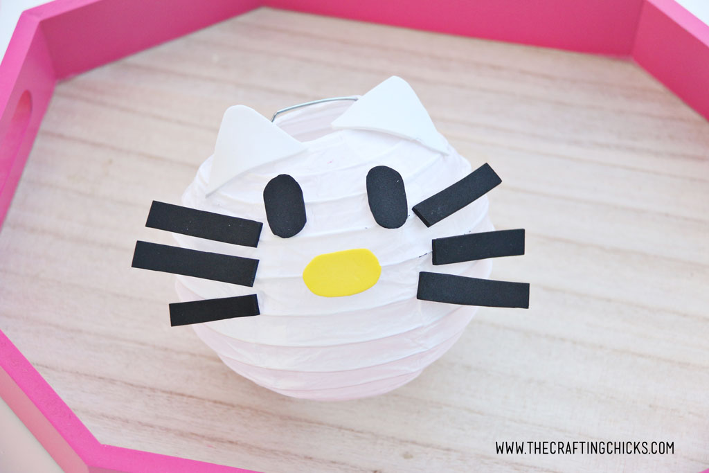 White foam kitty ears added to White mini paper lantern with cut out foam shapes to make Hello Kitty DIY Paper Lanterns