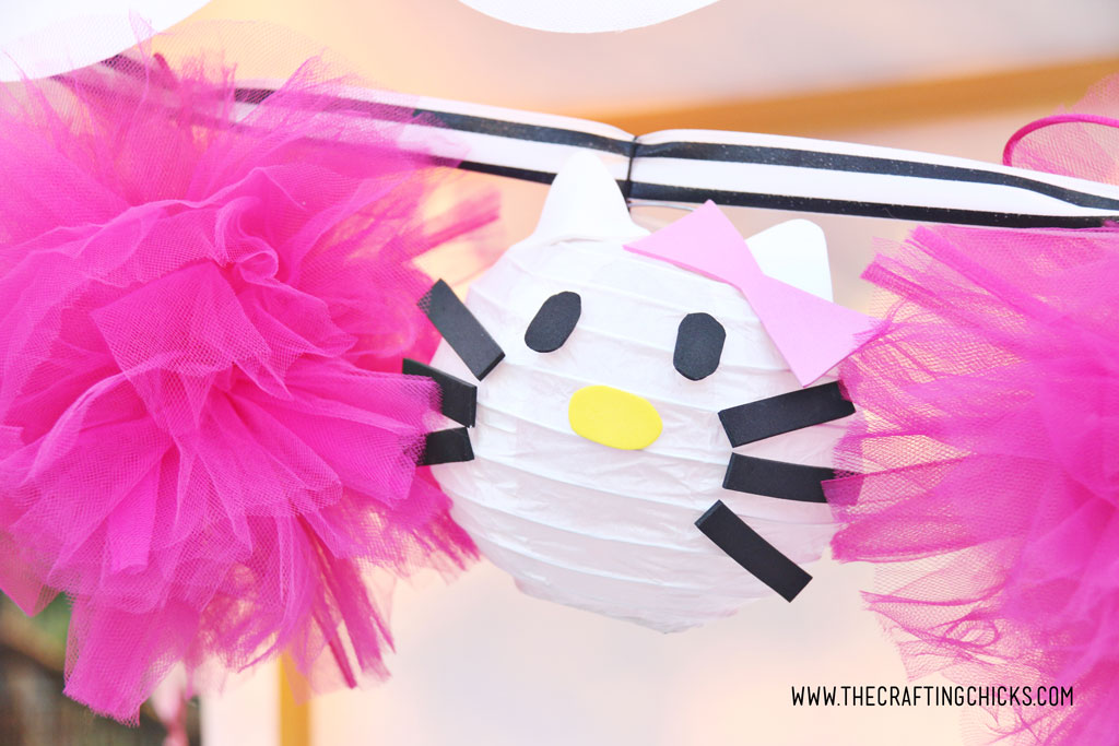 Hot Pink Tulle Pom-Pom and Hello Kitty DIY Paper Lanterns strung together on a black and white striped satin ribbon to make a garland