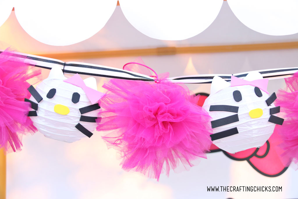 Hello Kitty Paper Lanterns strung up on a garland with bright pink pom poms