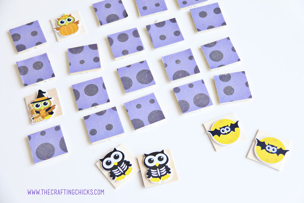 Purple paper covered wooden squares laid out for a game of Halloween Owl Memory