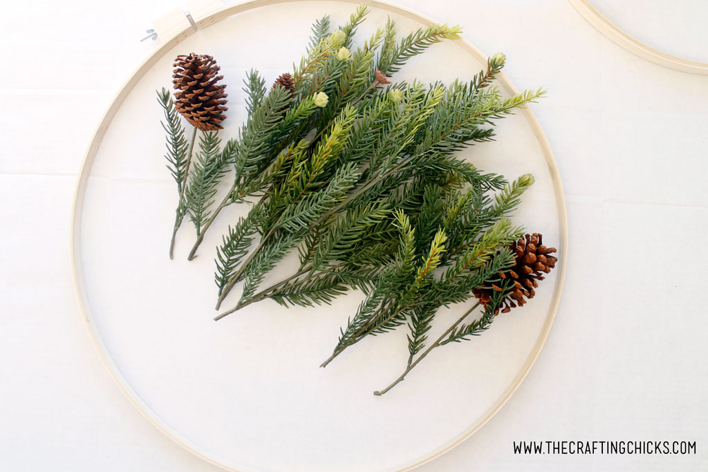 Faux pine branches or picks, separated inside an embroidery hoop.
