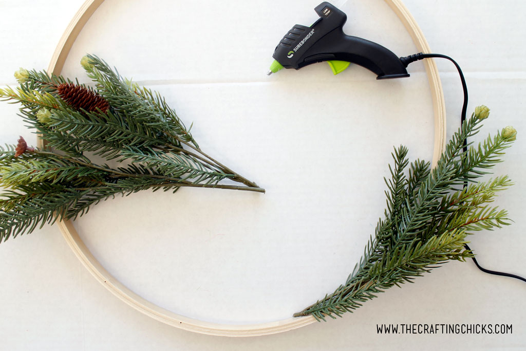 Using a hot glue gun to attach faux pine branches to an embroidery hoop to make a hoop wreath.
