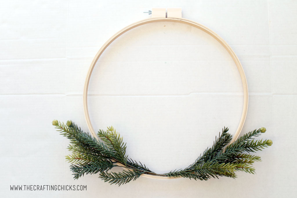 Embroidery hoop made into a wreath with faux pine branches.