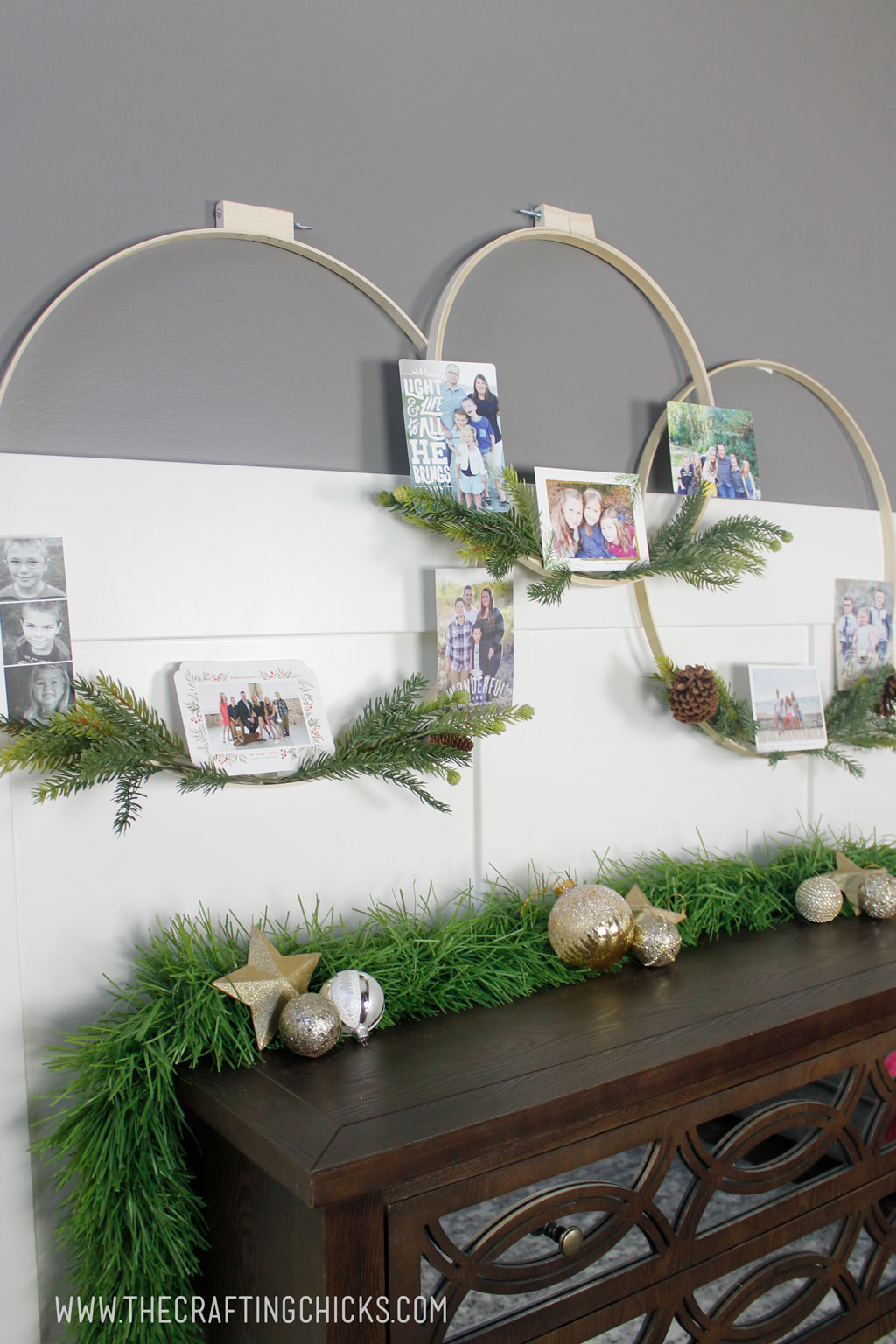 Embroidery hoop wreaths with faux pine hanging on a wall and decorated with Christmas cards