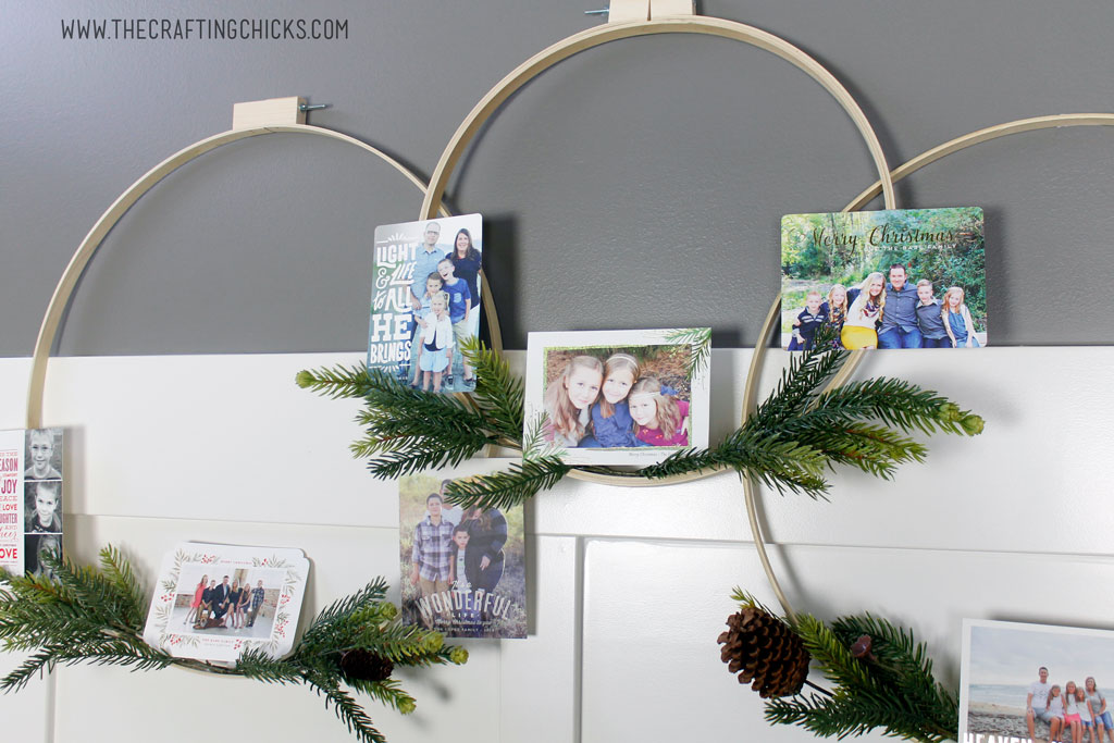 Holiday Hoop Wreath decorated with pine sprigs and Christmas cards.