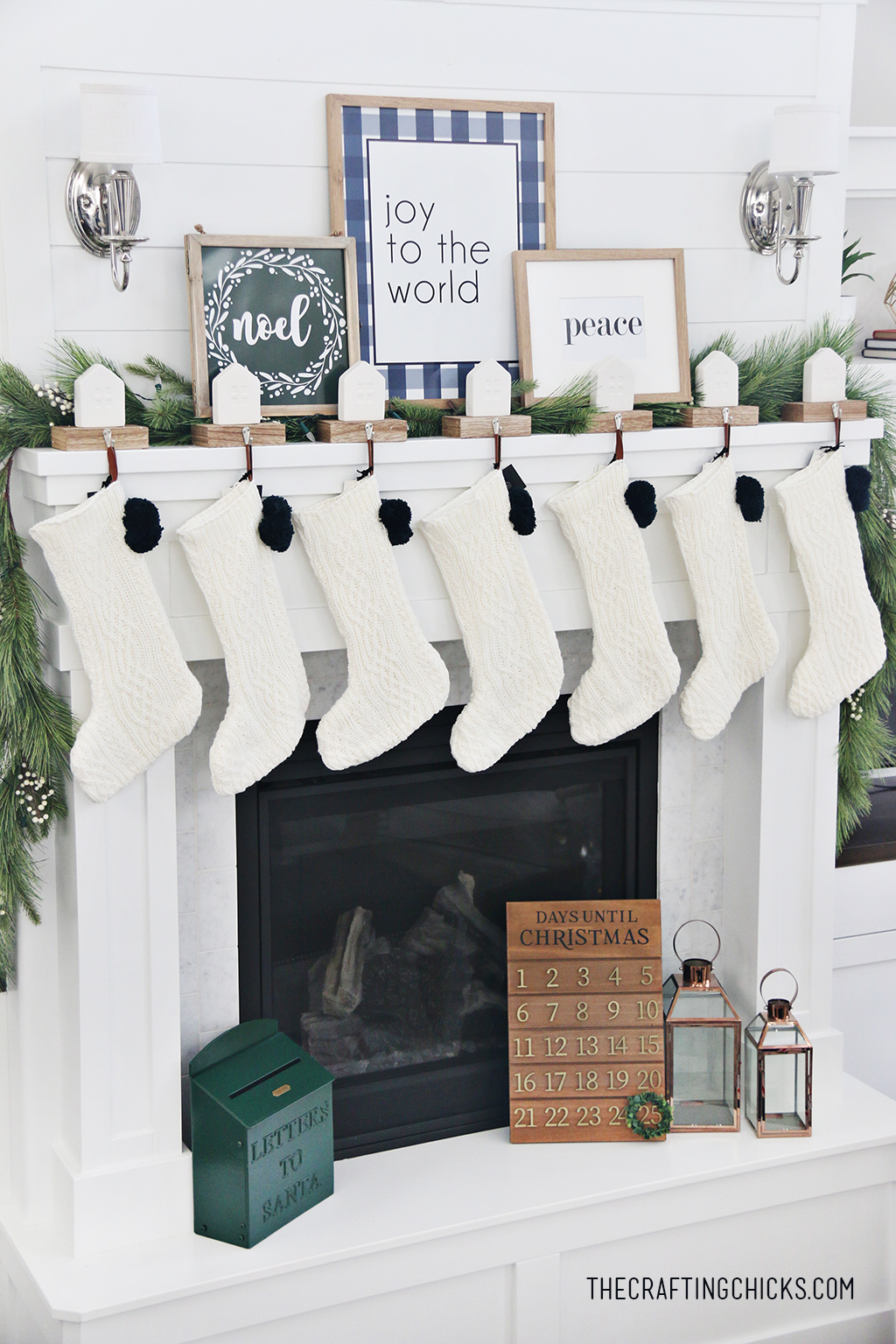 White fireplace mantel decorated for Christmas with Christmas prints in frames and white knit stockings.