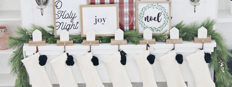 White fireplace and mantel decorated with white knit stockings and Christmas prints in frames.