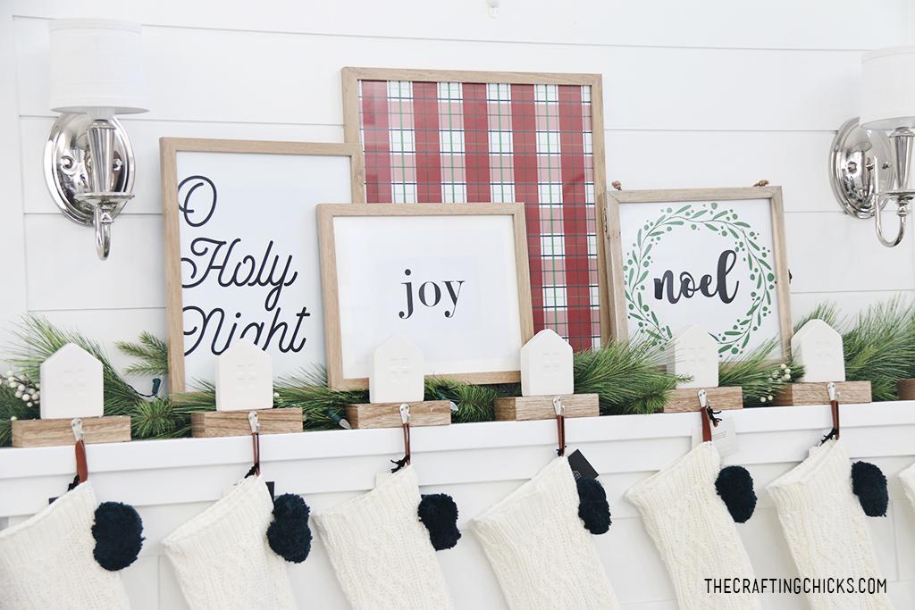 Joy print framed on a Christmas mantel with other Christmas home decor prints on a white mantel.