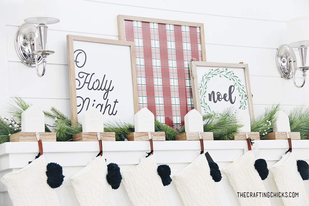 Noel Wreath print framed on a white mantel next to a red plaid background print and Oh Holy Night print.