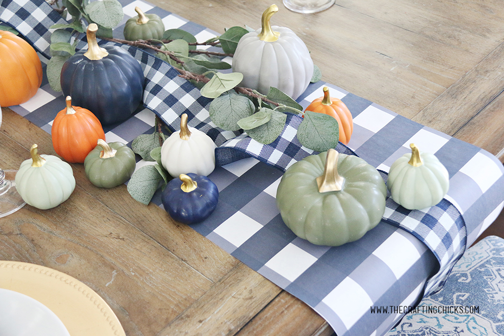 Thanksgiving table with mini pumpkins and navy and white check printable table runner.