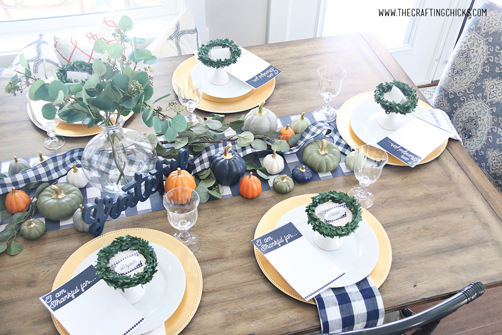 Styled Thanksgiving table with gold chargers and white plates. Navy and white check print napkins and table runner. With mini pumpkins and small wreaths to decorate.