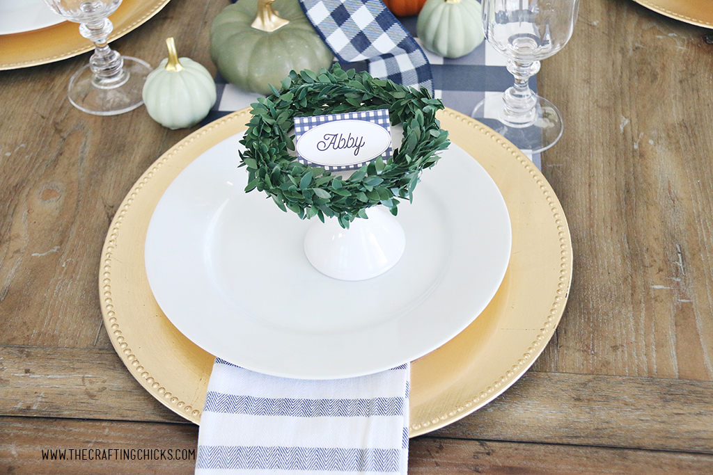 Thanksgiving navy and white check, printable place cards. Styled on a gold charger and white plate and decorated with a green wreath.