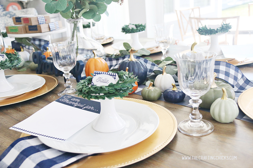 Thanksgiving table styled with navy and white check print and mini pumpkins and gold chargers.