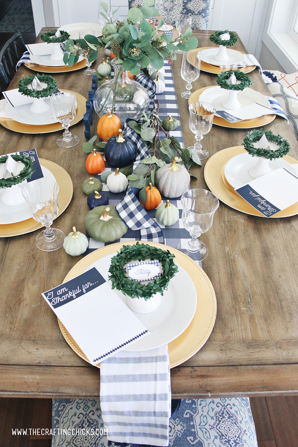 Thanksgiving table set with gold chargers and white plates. Printable navy and white placecards with wreaths and mini pumpkins.