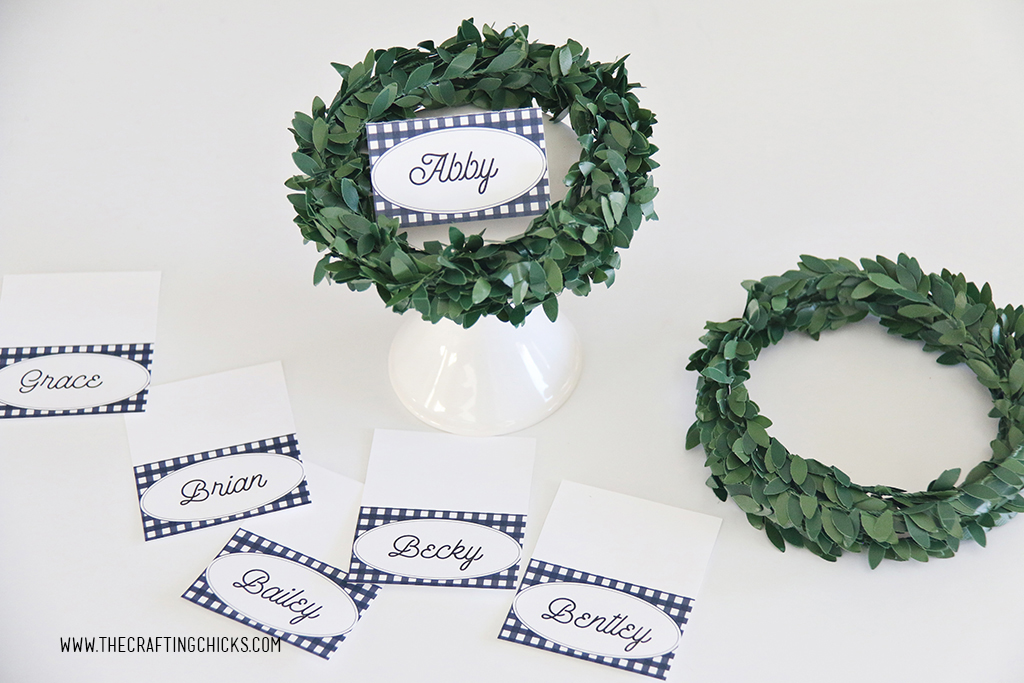Thanksgiving navy and white check printable place cards on a white stand with a wreath on them.
