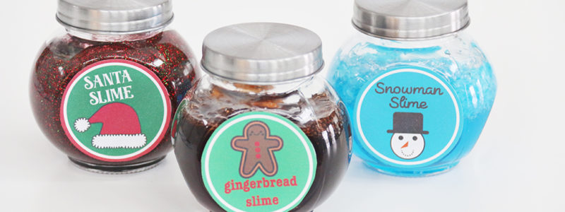 Santa Slime, Gingerbread Slime, and Snowman Slime in glass jars with lids on a white background