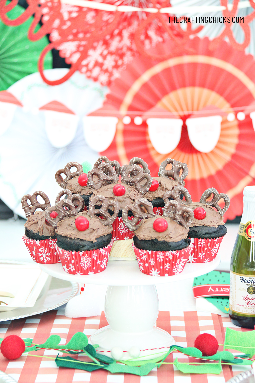 Reindeer cupcakes on decorated party table with red and green paper fan background.