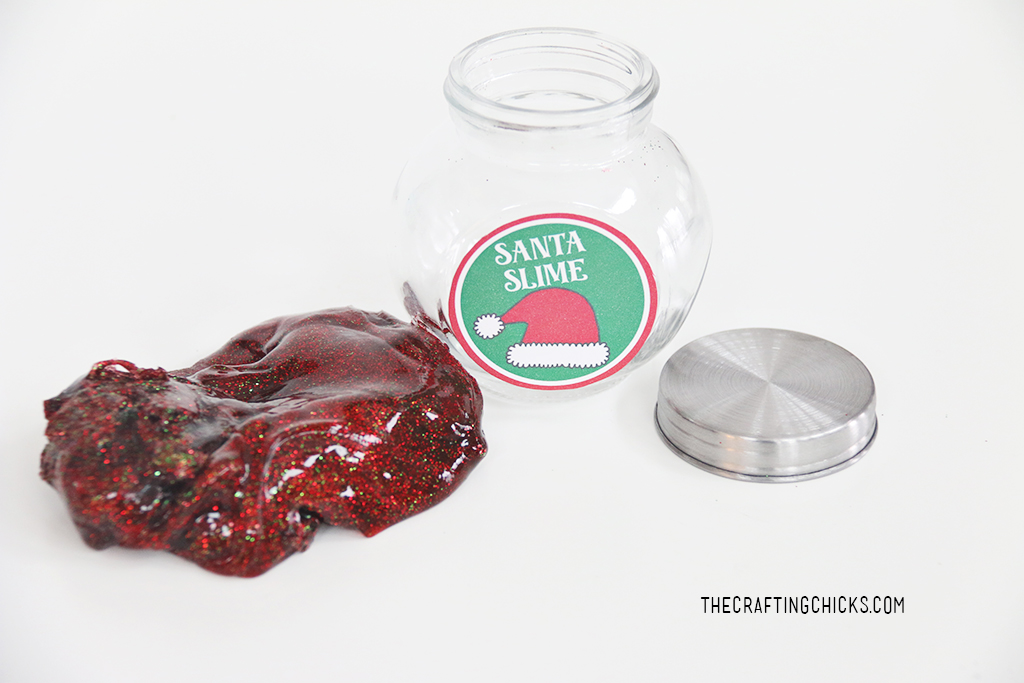 Read slime with red and green glitter. Small clear glass jar and lid on the side for Santa Slime