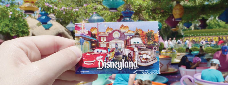 Disneyland ticket in front of teacup ride.