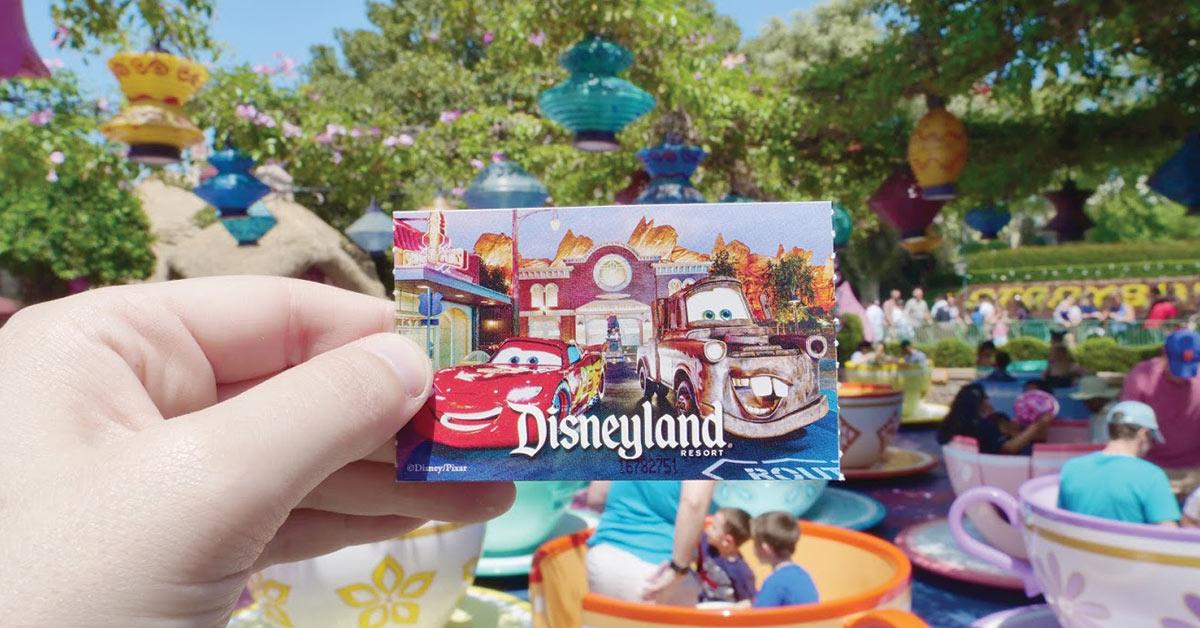 Disneyland ticket in front of teacup ride.